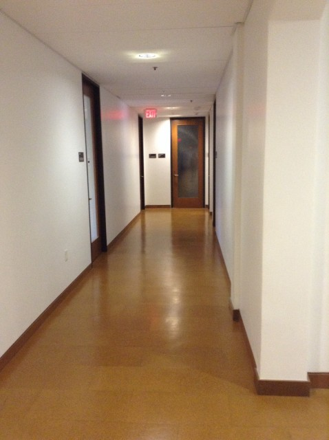 At the end of the corridor on the left